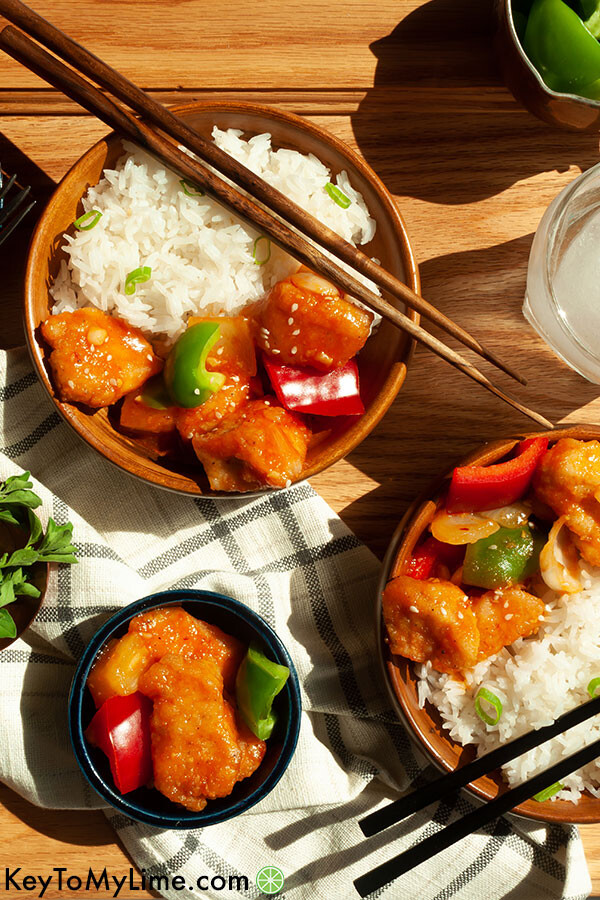 A close up image of sweet and sour chicken with chopsticks in a bowl.