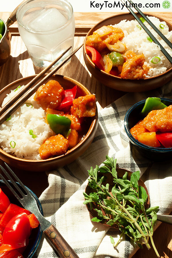 A side view of sweet and sour chicken in shallow bowls.