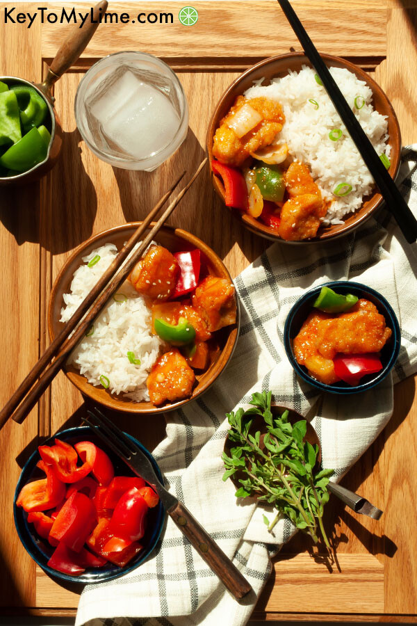 A display of sweet and sour chicken on plates with a wood background.