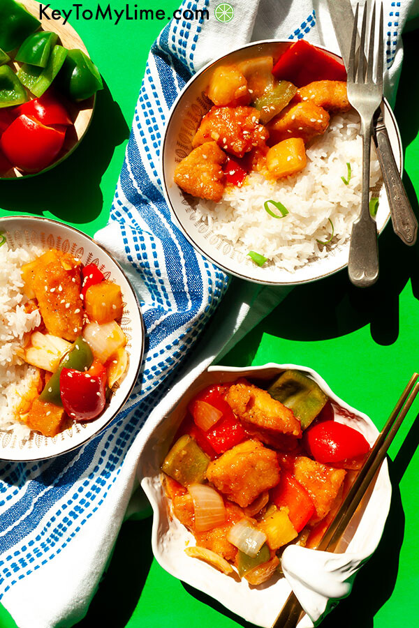 Three plates of sweet and sour chicken on a green background.