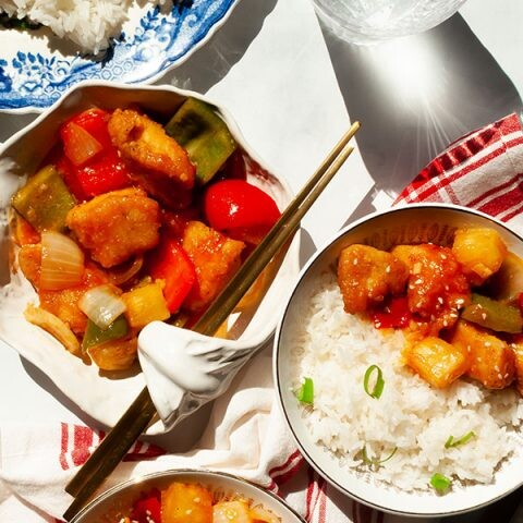 Sweet and sour chicken on a plate next to a glass of water with light shining through it.