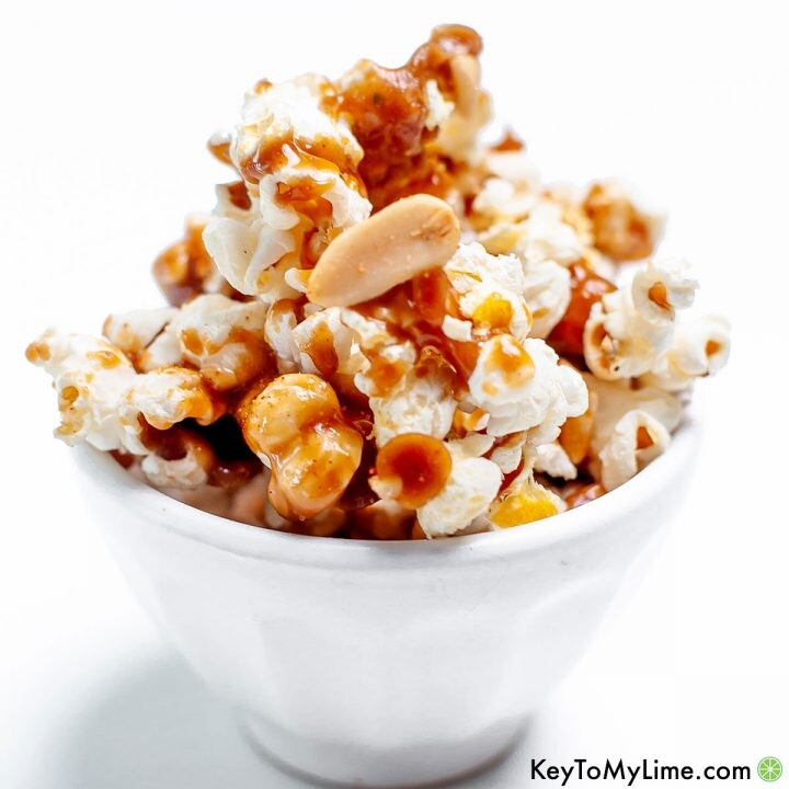 A close up image of spicy caramel popcorn in a simple white bowl.