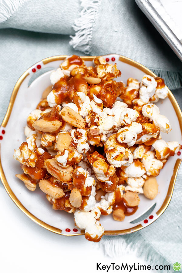 Spicy caramel popcorn in a small white and gold rimmed bowl.