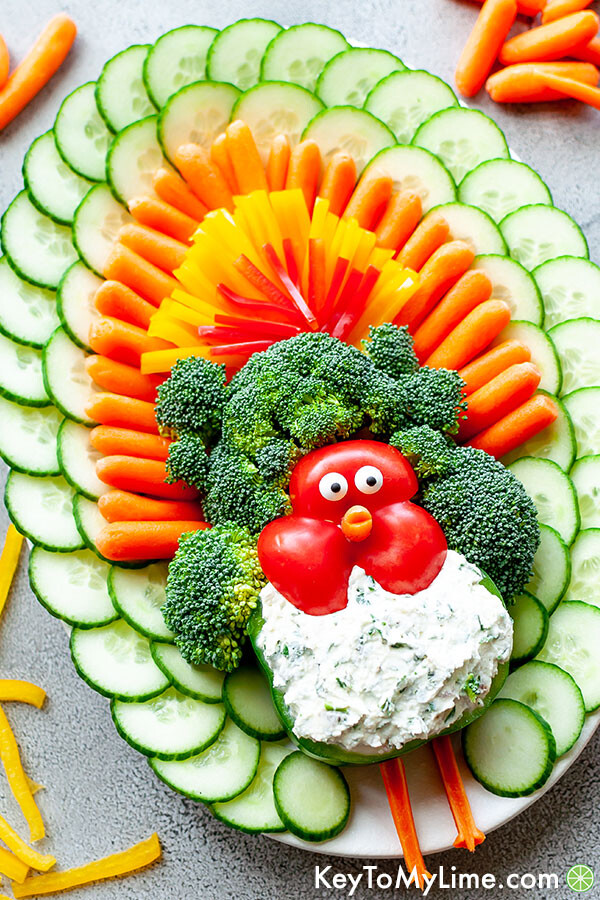 An angled image of a turkey shaped vegetable platter surrounded by scattered sliced vegetables.