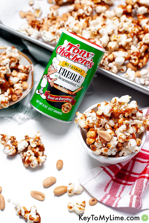 Spicy caramel popcorn next to a can of Tony Chachere's Creole Seasoning.