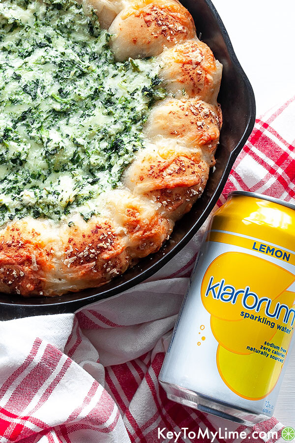 Spinach wreath dip next to a can of Klarbrunn lemon sparkling water.