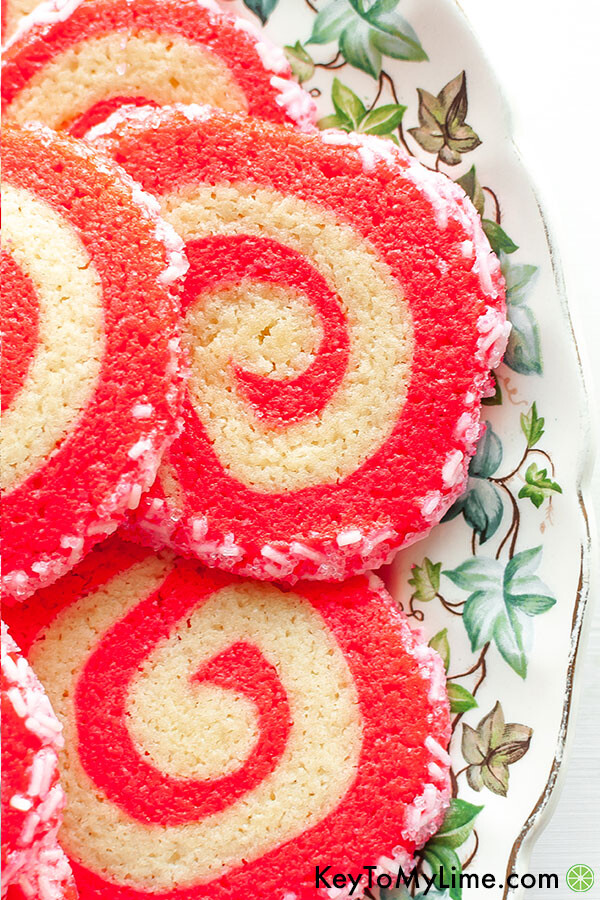 Christmas pinwheel cookies on a holiday platter decorated with green leaves.