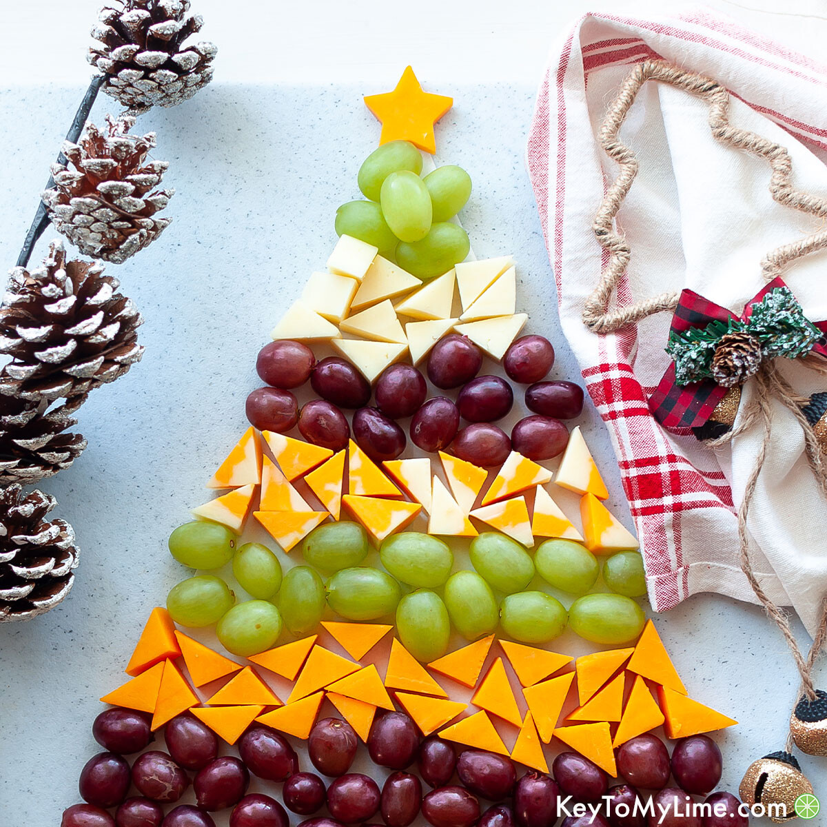 A holiday cheese platter surrounded by pine cones and a red plaid napkin.