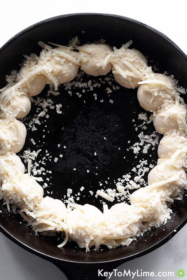 Raw biscuit dough bowls around the perimeter of a cast iron skillet.