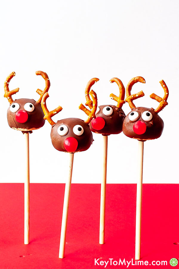 4 reindeer cake pops against a red and white background.