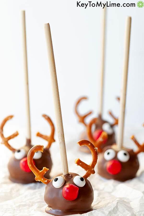 Reindeer cake pops on a sheet of parchment paper.