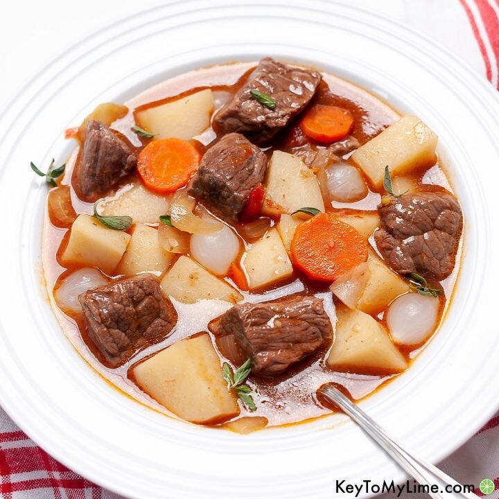A white bowl filled with potato, vegetable, and beef Mulligan stew.