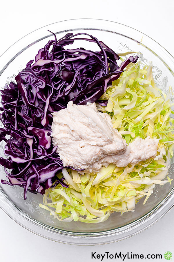 Shredded coleslaw with coconut slaw dressing before mixing in a big clear bowl.