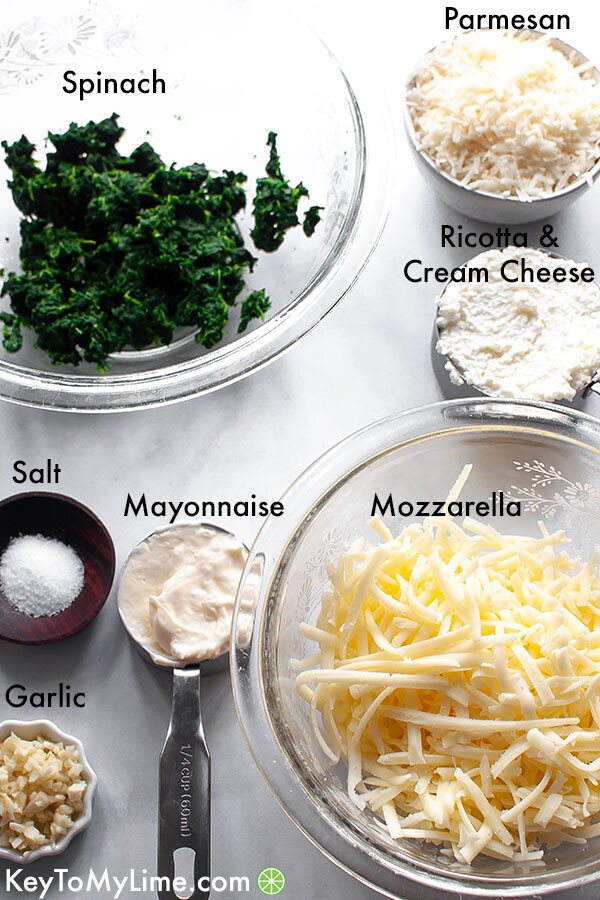 The ingredients for spinach dip in labeled individual jars.
