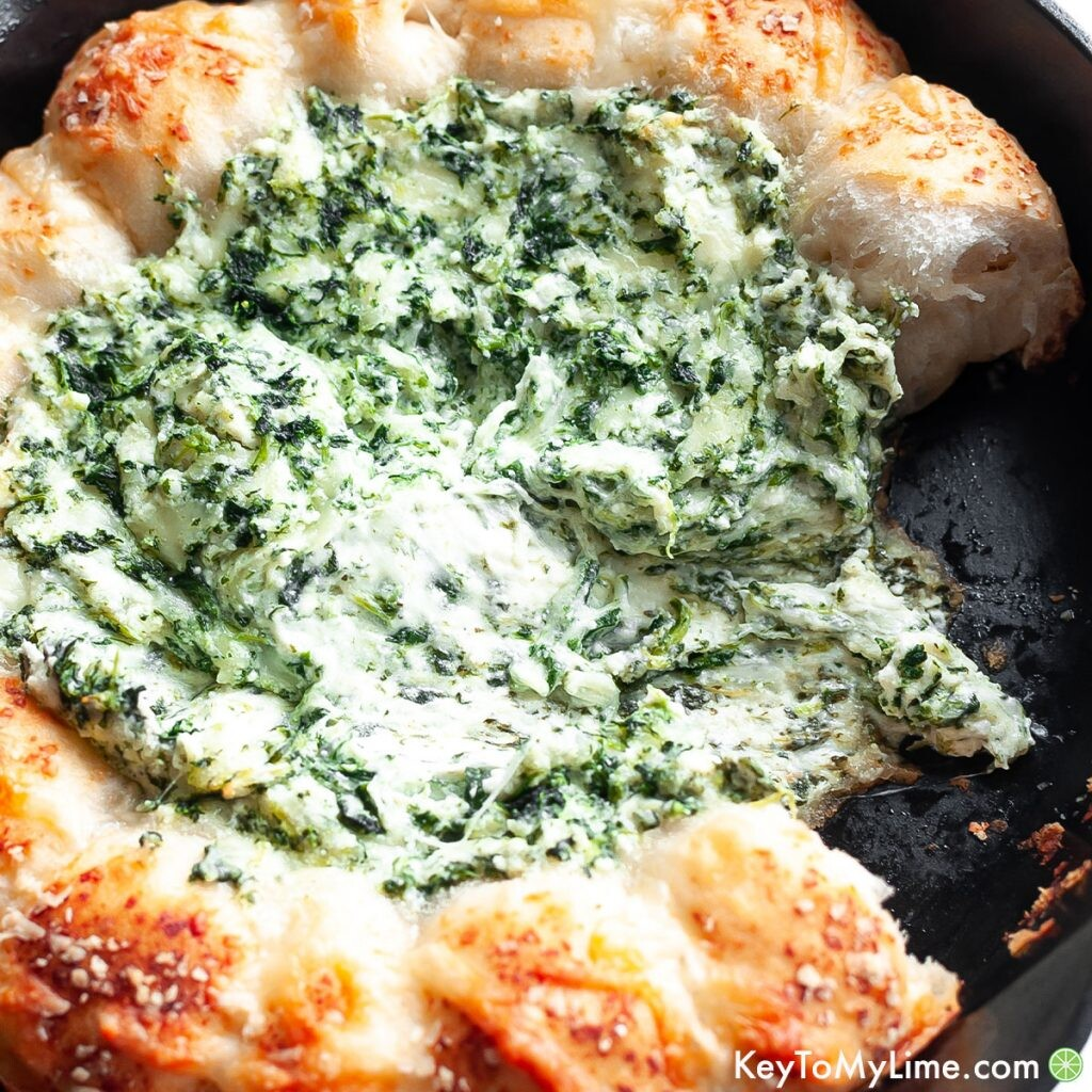 Hot spinach dip with a bite missing.