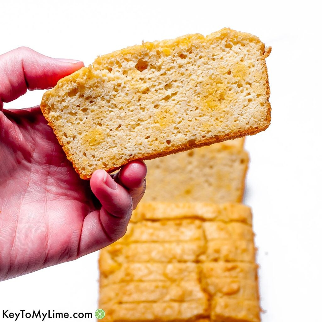 A hand holding a slice of keto bread.