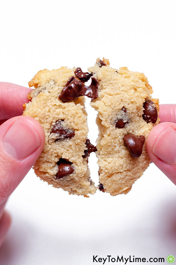 A hand pulling apart two halves of a keto cookie with melted chocolate stretching between the halves.