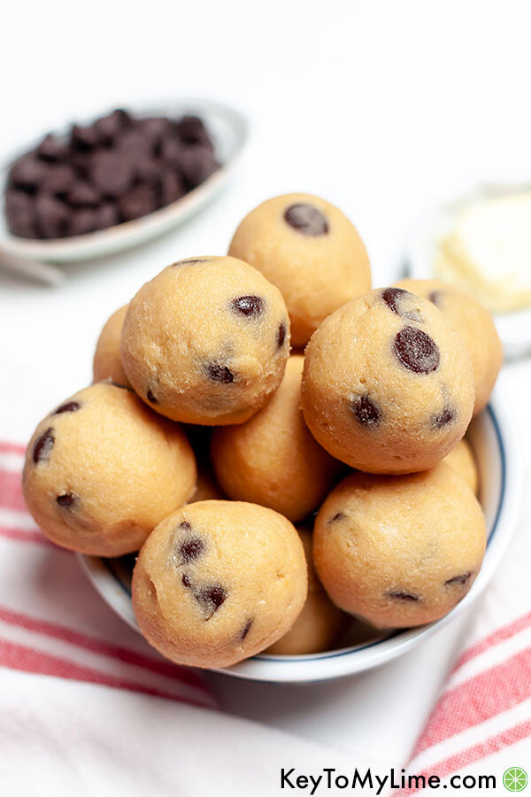 Keto cookie dough next to a pile of chocolate chips.