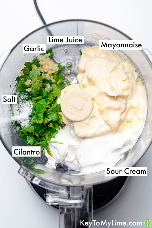 Labeled cilantro lime sauce ingredients in a food processor.