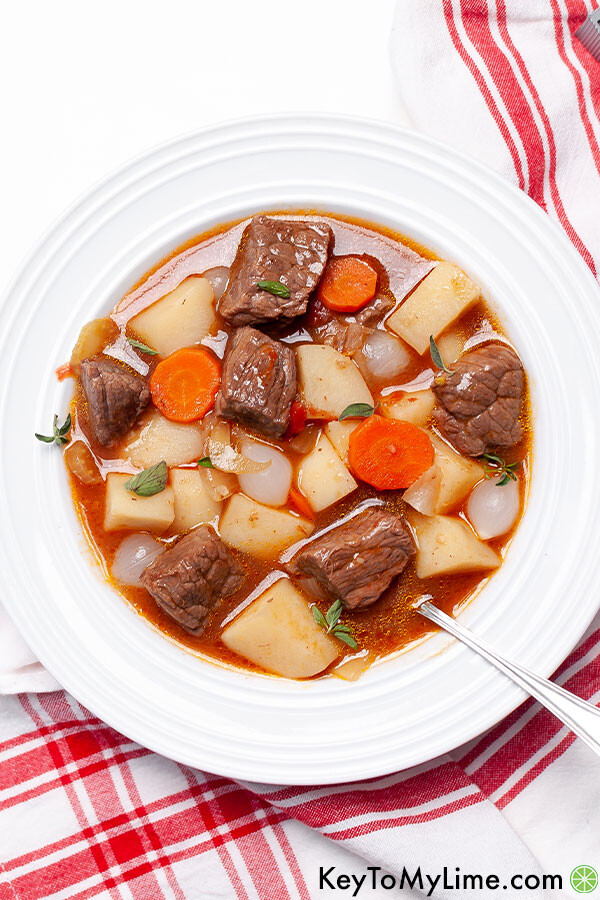 Mulligan stew in a white shallow bowl.