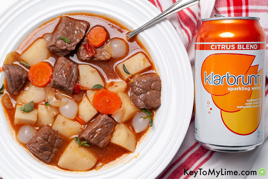 Beef stew next to a can of Klarbrunn sparkling water.