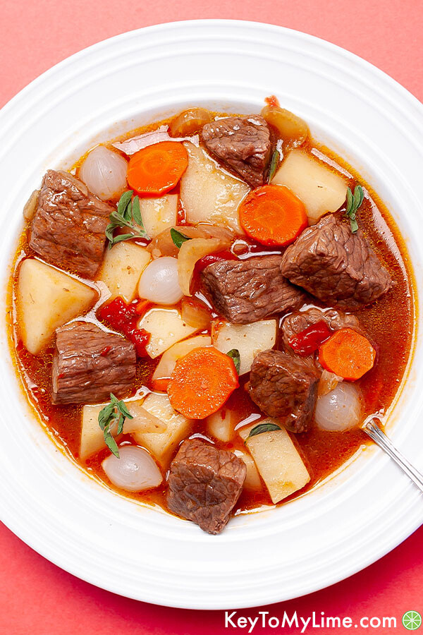 A close up of a bowl of Mulligan stew on a peach background.