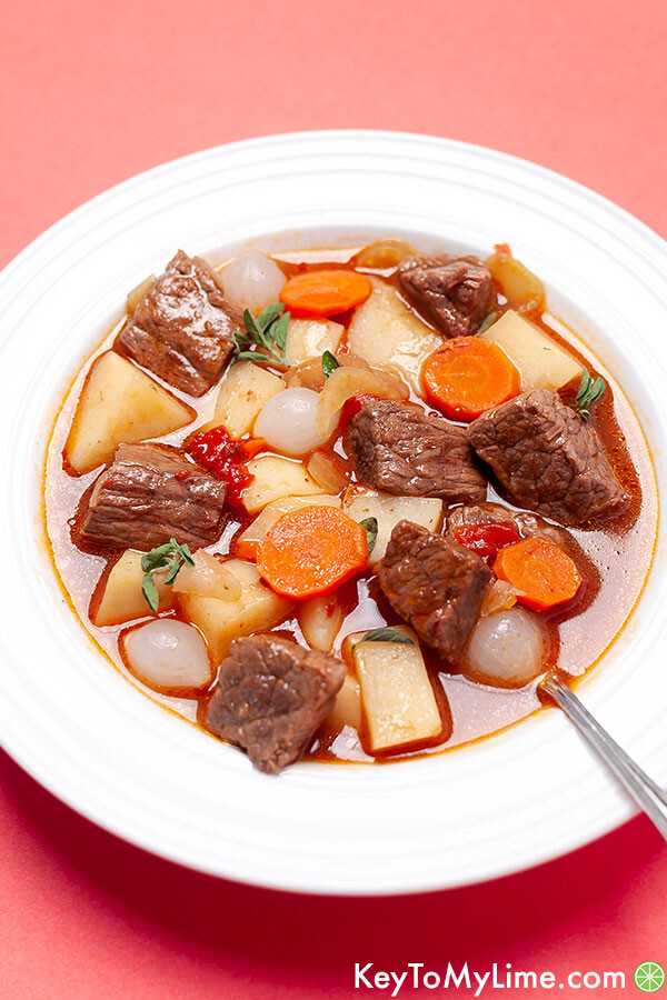 A side image of a bowl of Mulligan stew on a peach background.