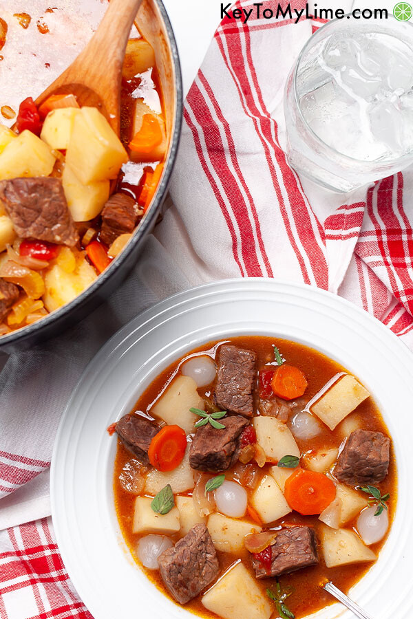A bowl of Mulligan stew on top of a red and white napkin.