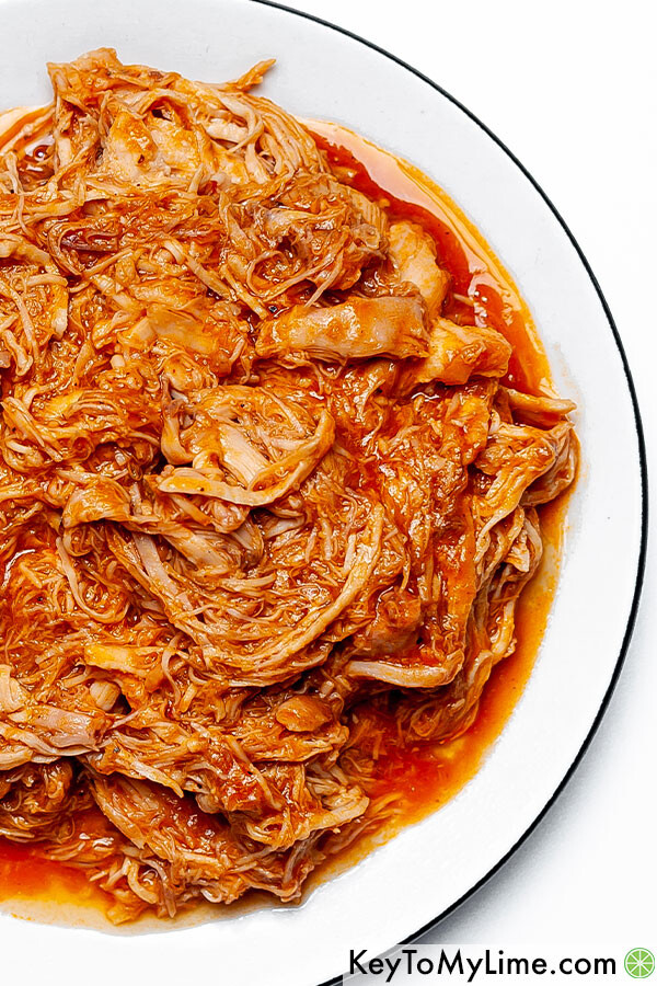 A close up of pulled bbq chicken on a plate.