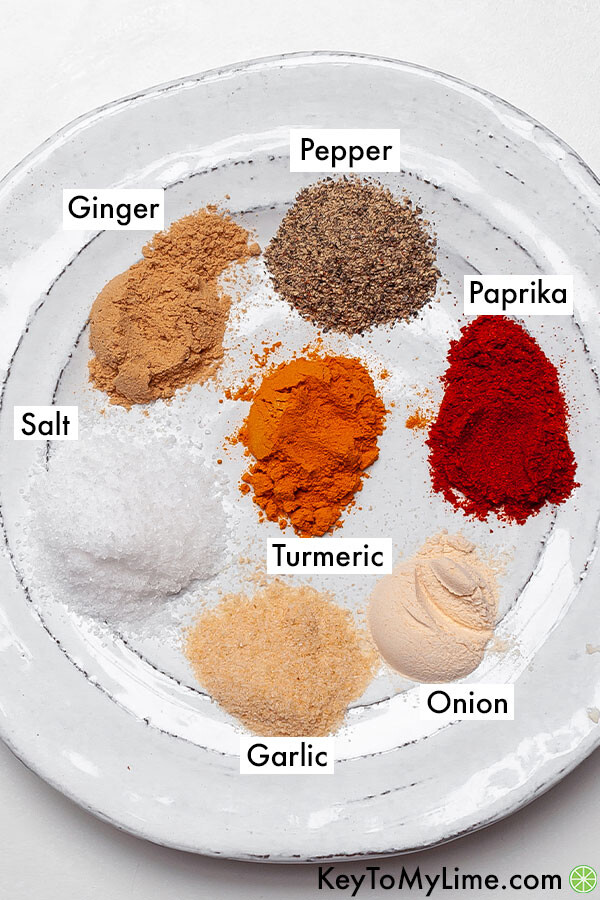 The spices to coat the chicken labeled on a plate.