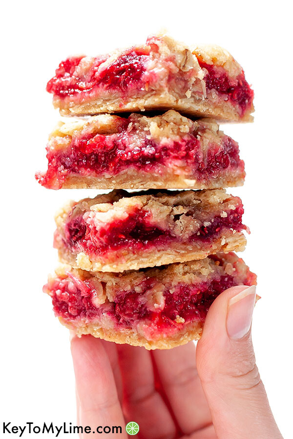 A hand holding a pile of four raspberry bars.