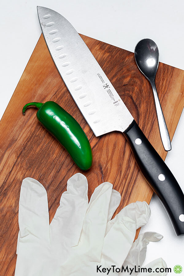 Rubber gloves, a knife, a spoon, and a jalapeno on a cutting board.