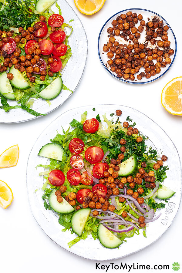 Two plates of salad topped with crispy roasted chickpeas.