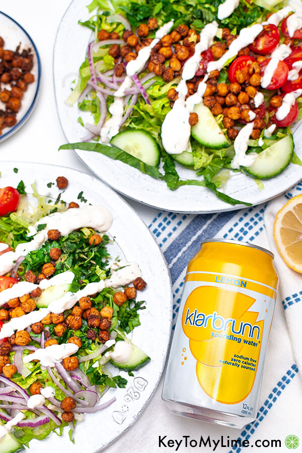 Two plates of salad next to a can of lemon sparkling water.