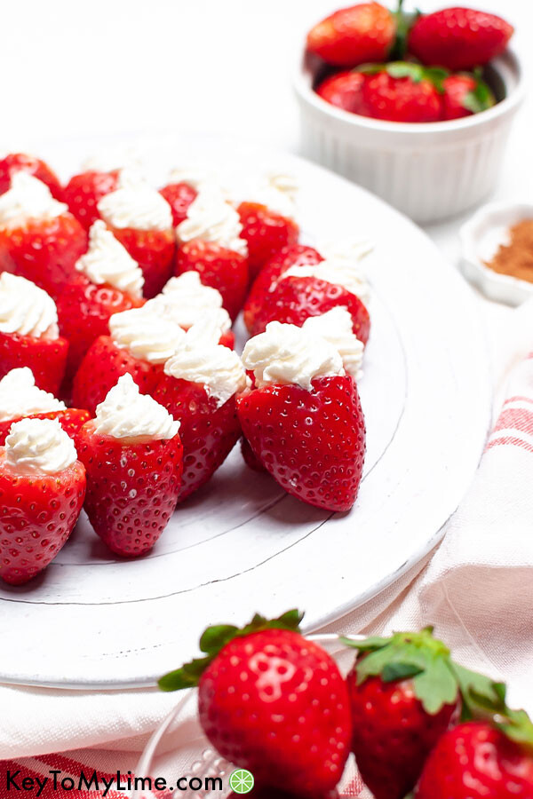 A side image of keto cheesecake stuffed strawberries on a white plate.