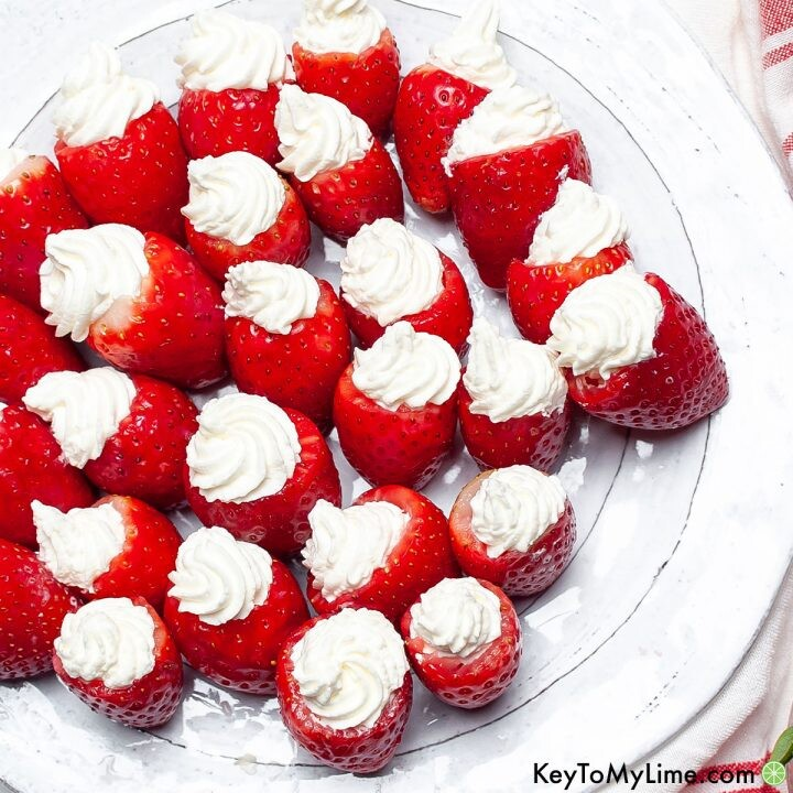 A white plate filled with keto cheesecake stuffed strawberries.