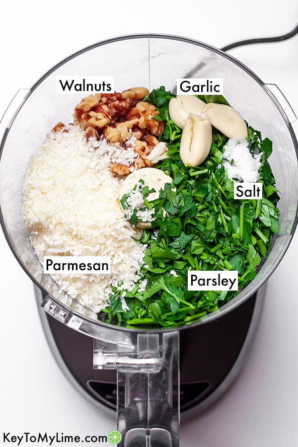 Labeled ingredients for parsley pesto in a food processor.