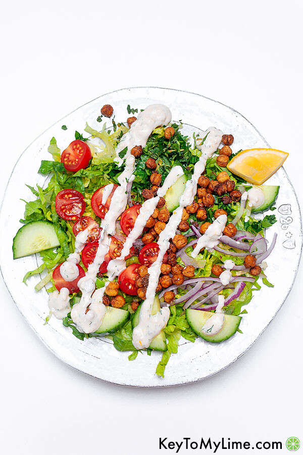 Chickpea salad with lettuce on a white plate.
