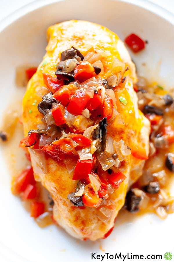 An overhead image of baked chicken breast with diced bell peppers on top.