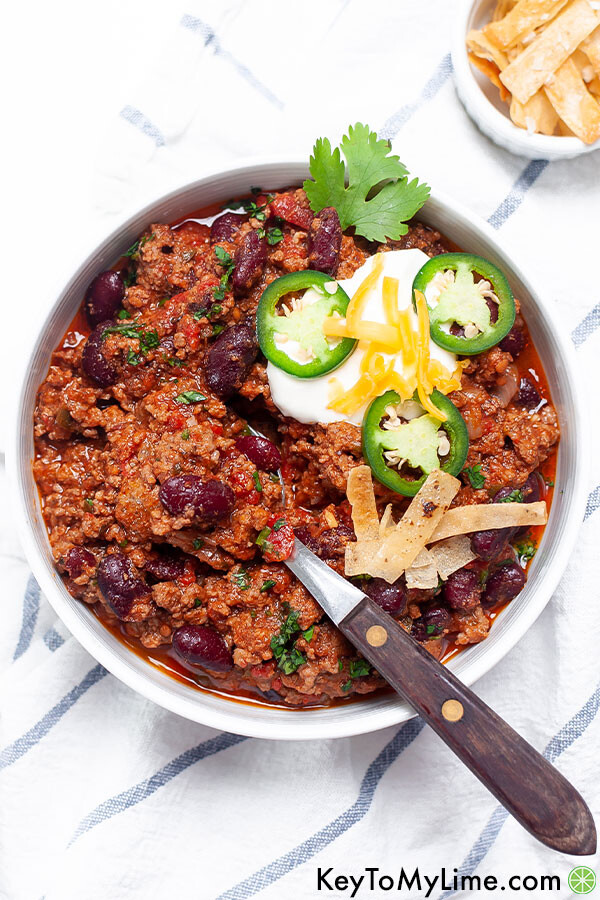 Chili con carne in a bowl with a spoon and toppings.
