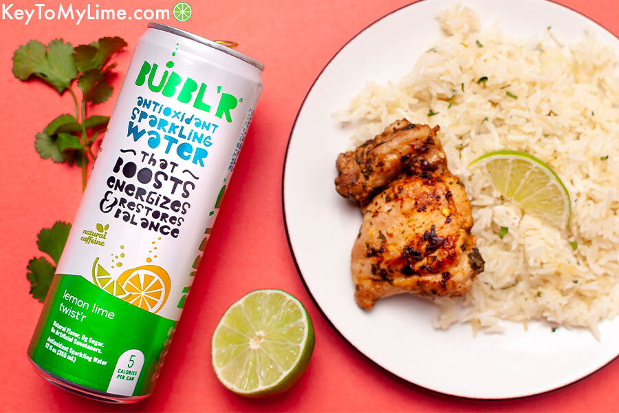 Cilantro lime chicken and rice next to a can of sparkling water on a peach colored background.