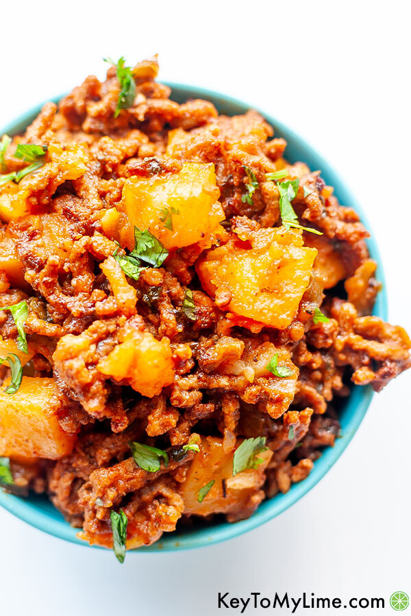 A close up image of Mexican ground beef with potatoes in a small blue bowl.