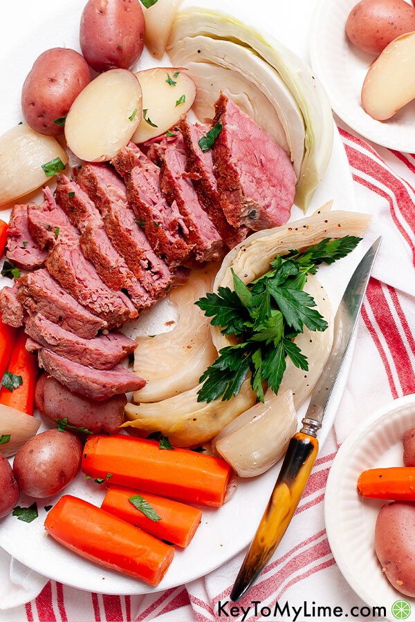 Corned beef with vegetables on a white platter.