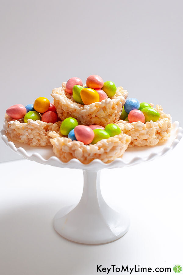 Rice Krispie Nests stacked on a white cake stand.