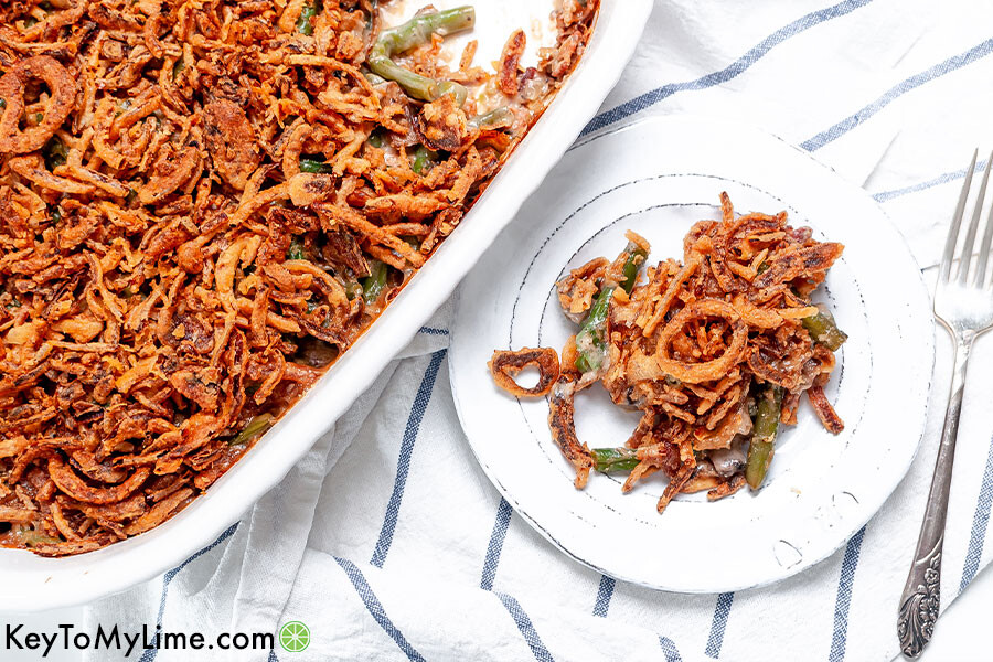 Cheesy green bean casserole in a baking dish and on a plate.