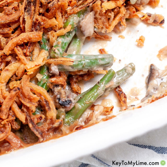 The best green bean casserole with bacon in a white baking dish.