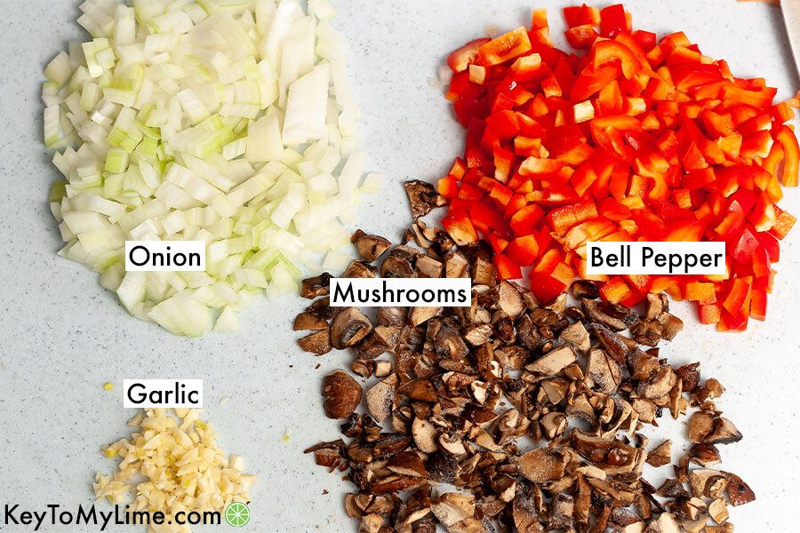 Labeled onion, bell pepper, garlic, and mushrooms on a cutting board.