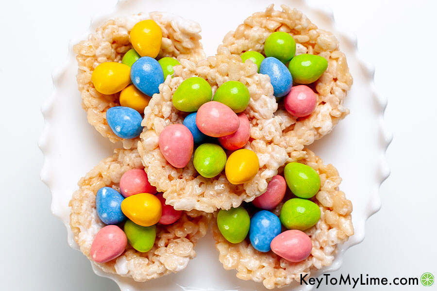 Rice Krispie nests with pink, green, blue, and yellow candy eggs.
