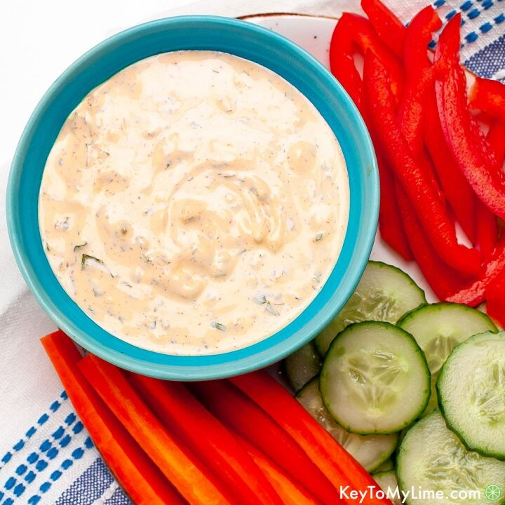 Spicy ranch in a small blue bowl surrounded by sliced carrots, cucumbers, and red bell pepper.