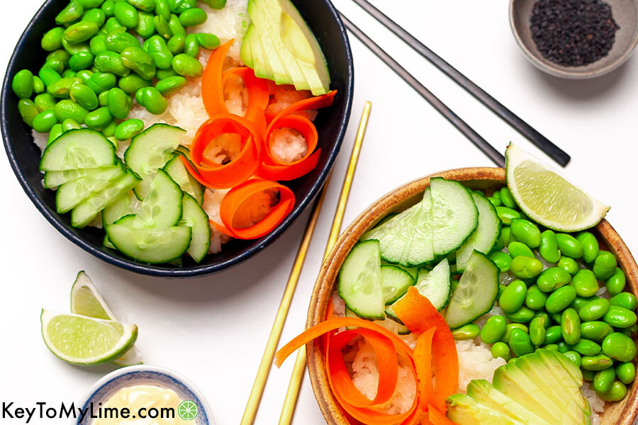 Vegetarian sushi bowls with carrot, avocado, cucumber, and edamame.